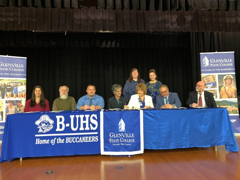 Representatives from Upshur County Schools and Glenville State College sign a Memorandum of Understanding for the innovative Home Grown Teacher and Dual Enrollment Programs on March 28 in the B-UHS Auditorium; (seated, l-r) Katie Yeager, Dr. Greenbrier Almond, Eddie Vincent, Dr. Debra Harrison, Dr. Sara Stankus, Dr. Victor Vega, and Dr. Jeff Hunter; (standing, l-r) Rachel Adams and Rachel Clutter