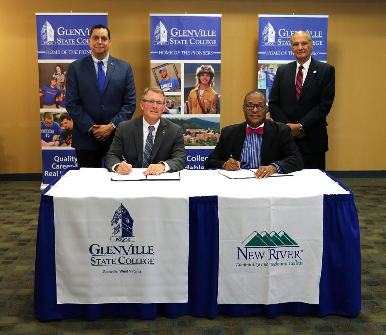 (seated) Glenville State College President Dr. Tracy Pellet and New River Community and Technical College President Dr. L. Marshall Washington sign agreement documents between the two institutions; (standing) GSC's Vice President for Academic Affairs Dr. Gary Morris and New River CTC Vice President for Academic Affairs Dr. Richard B. Pagan