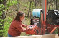 Glenville State College student Gabrielle Dean cuts a log down into boards using the College's portable Wood-Mizer bandsaw.
