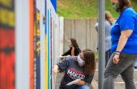 Glenville State College students add to the colorful bookshelf mural behind the Robert F. Kidd Library